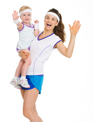 Smiling mother and baby in tennis clothes greeting