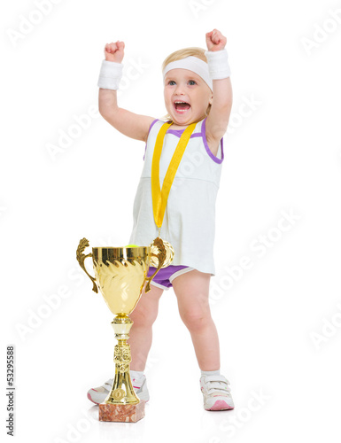Happy baby in tennis clothes with medal and goblet