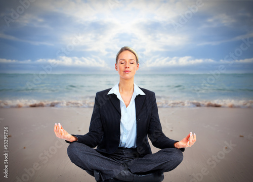 Business woman doing yoga on the beach.