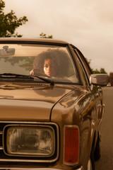 Retro 70s fashion african american woman driving in gold seventi