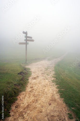 signpost with fog and a pathway