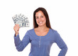 Hispanic female holding dollars while standing