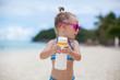 Little adorable girl in swimsuit shows suntan lotion bottle