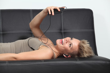 Woman at home listening to the music from a smartphone
