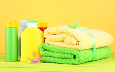 Baby cosmetics and towels on wooden table, on yellow background