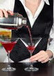 Barmen hand with shaker  pouring cocktail into glasses,