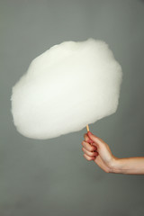 Hand holding stick with cotton candy, on color background
