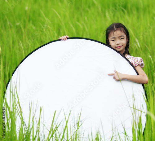 Cute little girl on neutral background holding sign