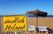Strand mit Schild - endlich Urlaub