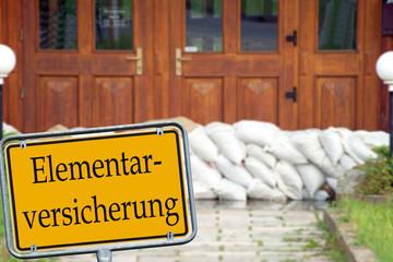 Sandsäcke und Schild - Elementarversicherung