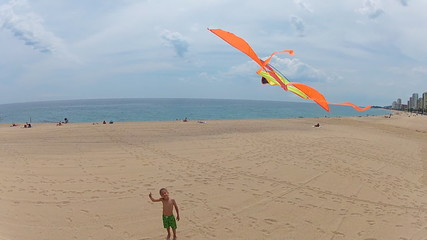 young boy flying a kite on the beach
