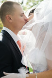 Groom kissing bride in lips outdoors