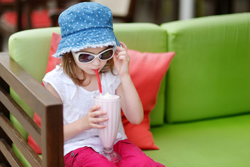 Adorable little girl drinking milkshake