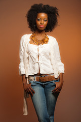 Vintage 70s fashion afro woman. White shirt and jeans against br
