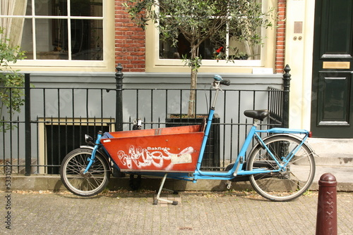 Tricycle against a facade of a house in Amsterdam