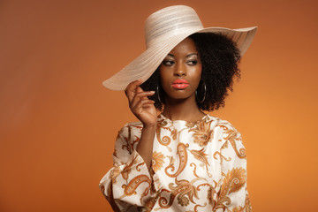 Retro 70s fashion afro woman with paisley dress and white hat. B
