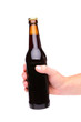 A hand holding up a brown beer bottle