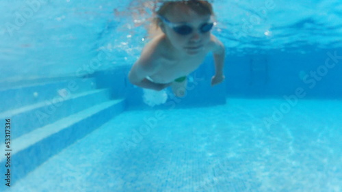 boy swimming underwater in pool outdoors
