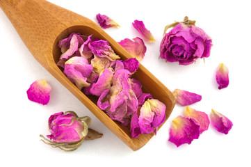 Wooden spoon filled by purple dried petals and buds of rose