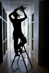 Silhouette of a janitor repairing broken lamp in office corridor