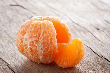 Raw skinned mandarin on wooden table