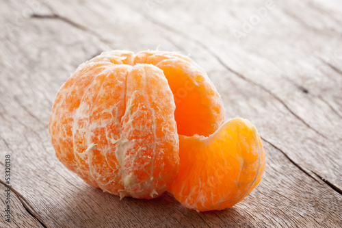 Raw skinned mandarin on wooden table