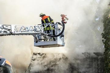 Drehleiter der Feuerwehr vor brennendem Haus