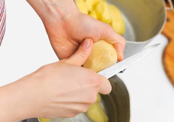 Woman cutting to peel potatoes. Kitchen working. Prepare food