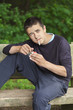 Boy with a cigarette on a bench in the park