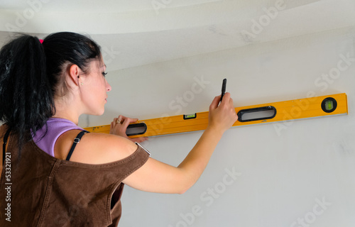 Woman using a spirit level while renovating
