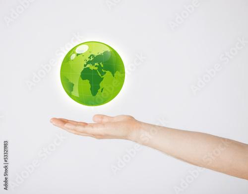 mans hand holding green globe