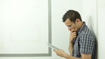 Pensive surprised man using tablet