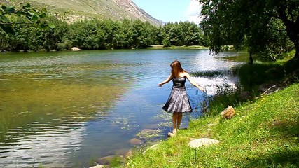 Young  girl in a dress dances on the shore of a mountain lake