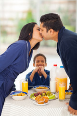 little boy is laughing when seeing parents kissing before breakf