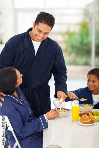 husband pouring milk for wife on breakfast table