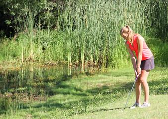 Female teen golfer in rough