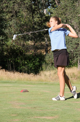 Female teen golfer after swing
