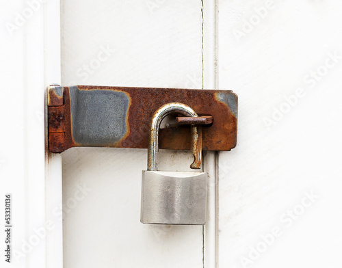 close up of a rusty padlock on a wooden door