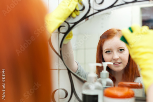 Teenager girl  cleans mirror
