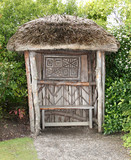 A Thatched Covered Wooden Garden Bench Seat.