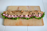 Sandwich with seeds, salami and salad