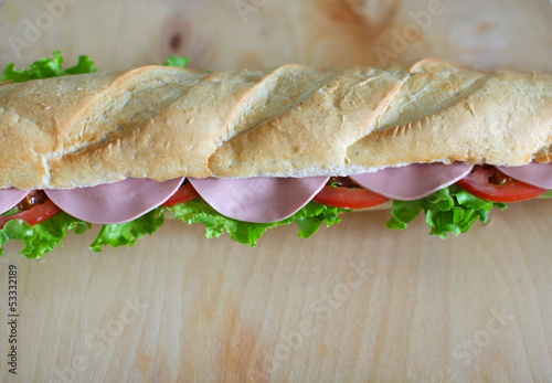 Sandwich baguette with chicken salami, salad and tomatoes