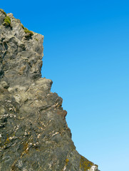 Jagged granite rock cliff edge and blue sky.