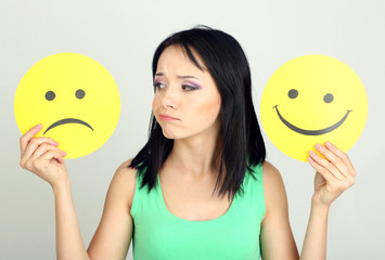 Young woman holding paper with sad and happy smiley