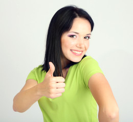 Happy young woman showing thumb up sign on grey background