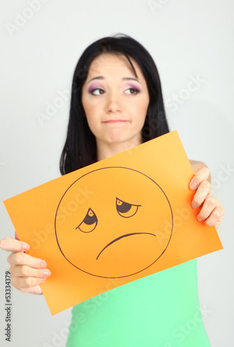 Young woman holding paper with sad smiley on gray background