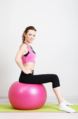 Portrait of beautiful young woman exercises with gym ball