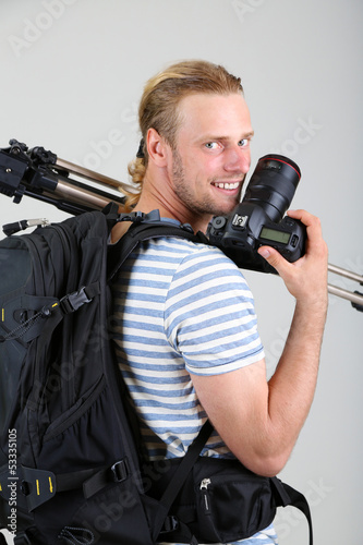 Portrait of handsome photographer with camera and tripod,