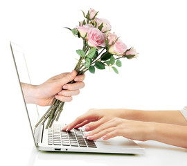 Male hand giving flowers to woman from laptop screen isolated