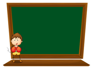 A boy in front of the empty blackboard